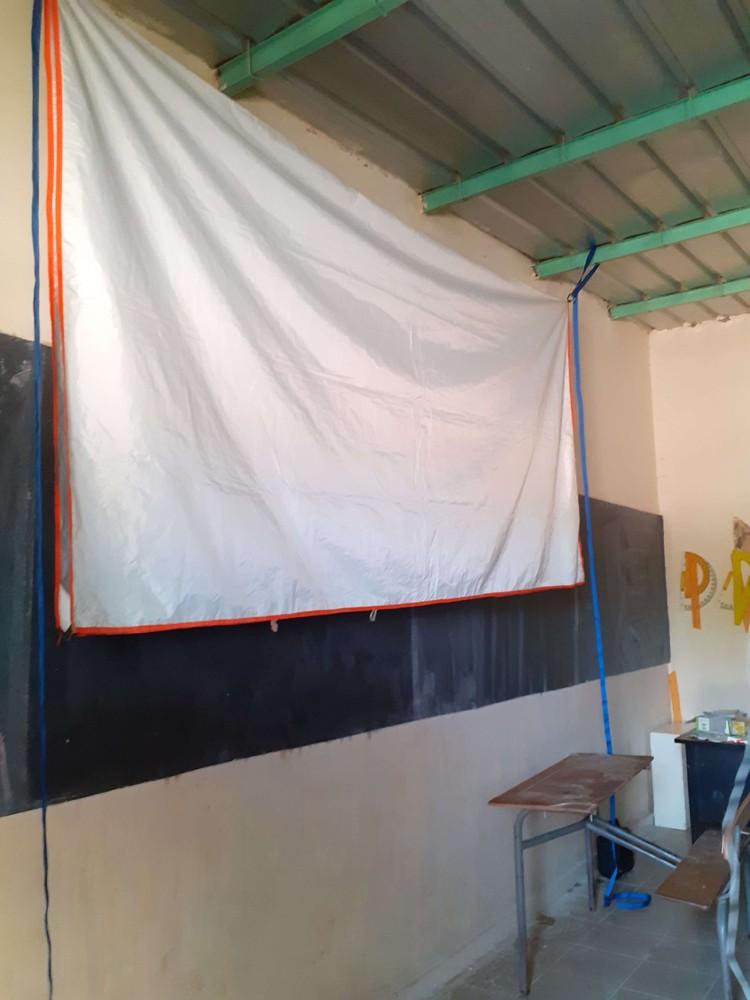 Un drap tendu sur le tableau noir en guise d'écran.